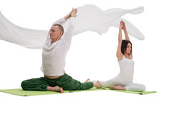 Man and woman doing yoga exercises in studio. Man and women doing yoga together sitting in splits on green mats in studio white cloth flying around Royalty Free Stock Image