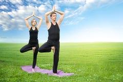 Man and woman doing yoga Stock Photo