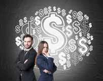 Man, woman and a dollar sign cloud. Portrait of two business partners standing with crossed arms near a blackboard with a giant dollar sign cloud drawing on it royalty free stock images