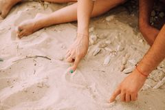 Man and woman draw their hands on the heart in the sand. Horizontal Stock Photos