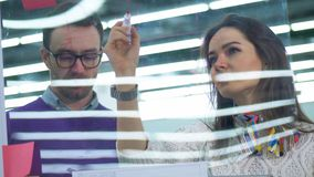 Man and woman draw on a transparent board, working together in a room. stock video