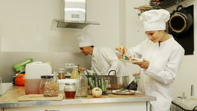 Man and woman dressed as chefs preparing food stock footage