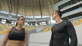 Athletes on Stadium. Man and woman dressed in black fitness clothing coming stadium, sportspeople training stock footage