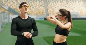 Athletes Warming up on Stadium. Man and woman dressed in black fitness clothing warming up on stadium before jogging exercise, sportspeople training stock video