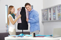 Man and woman dressing dress form Stock Images