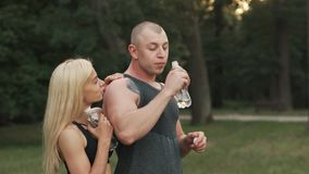 Sports couple drinking water after workout in park stock footage