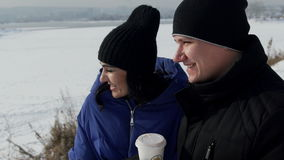 Man and woman drink coffee in picturesque place outdoors. Adult female with long dark hair, long eyelashes, black knitted cap, blue jacket with hood walk with stock footage