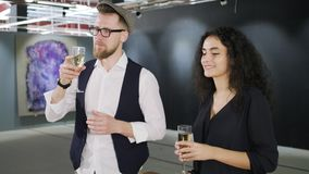 Man and woman are drinking champagne on opening of gallery and viewing pictures. Two visitors of modern fine art museum are admiring a picture. They are standing stock footage