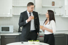 Man and woman drinking juice at the kitchen stock photos