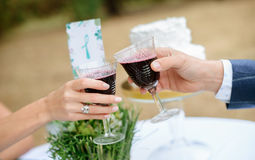 Man and woman drinking red wine. close-up hands with glasses. Stock Photography