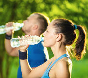 Man and woman drinking water from bottle after Stock Photography