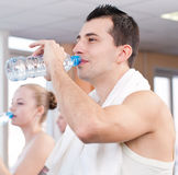 Man and woman drinking water after sports in gym Stock Image