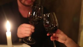 A man with a woman drinking wine in a restaurant by candlelght stock footage