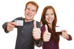 Man and woman with drivers licence. Young men and happy women with drivers licence holding their thumbs up royalty free stock photos