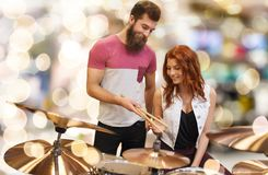 Man and woman with drum kit at music store. Music, sale, people, musical instruments and entertainment concept - happy men and women with drum kit at music store Stock Image