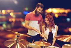 Man and woman with drum kit at music store. Music, sale, people, musical instruments and entertainment concept - happy men and women with drum kit at music store Royalty Free Stock Photography