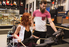 Man and woman with drum kit at music store Stock Photo