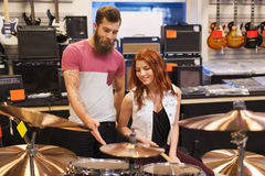 Man and woman with drum kit at music store Royalty Free Stock Photo