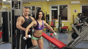 Man and woman with dumbbell flexing muscles in gym. HD stock footage