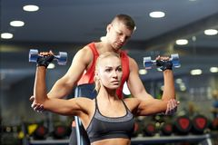 Man and woman with dumbbells in gym Royalty Free Stock Photo