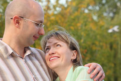 Man and woman in early fall park. Man is embracing smiling woman and looking at her Stock Images