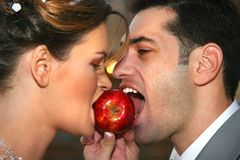 The man and the woman eat an apple. The enamoured guy and the girl eat a beautiful red apple Stock Photo