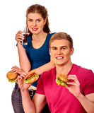 Man and woman eating big sandwich with drink.  Isolated. Royalty Free Stock Photos