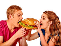 Man and woman eating big sandwich. Isolated Stock Photography