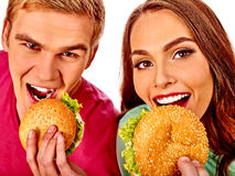 Man and woman eating big sandwich. Isolated Royalty Free Stock Photos