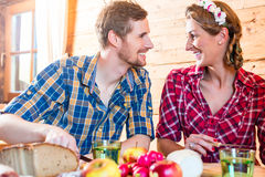 Man and woman eating food in mountain cabin Royalty Free Stock Images