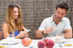 Man and woman eating in garden. Happy couple having food in garden while women is texting on phone Royalty Free Stock Photos