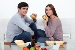 Man and woman eating hamburgers Stock Photo