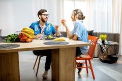 Man and woman eating healthy food at home royalty free stock image