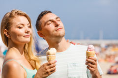 Man and woman eating ice cream on beach Royalty Free Stock Photo