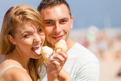 Man and woman eating ice cream on beach Stock Photography