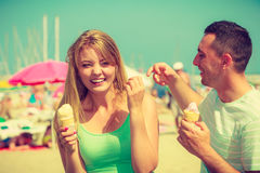 Man and woman eating ice cream on beach Stock Photo