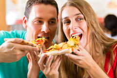 Man and woman eating a pizza Royalty Free Stock Image