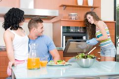 Man and woman eating salad and woman at the oven Stock Photography