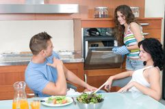 Man and woman eating salad and woman at the oven Royalty Free Stock Photo