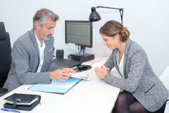 Man and woman either side office desk Stock Photos