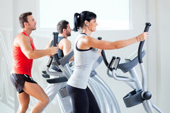 Man and woman with elliptical cross trainer at gym royalty free stock photography