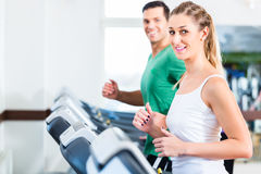 Man and woman on elliptical trainer in gym Royalty Free Stock Images