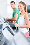 Man and woman on elliptical trainer in gym Royalty Free Stock Photo