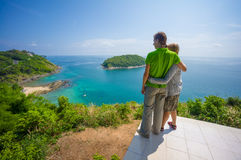 Man and woman embraces on tropical island cliff with small beach Stock Photo