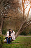Man and woman embracing in autumn park sitting on a tree hiding Royalty Free Stock Photo