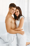 Man and woman embracing in bedroom Stock Photos