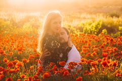 Man and woman embracing in poppy field on the dusk. Man and women embracing in poppy field on the dusk, countryside Malta royalty free stock photos