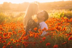 Man and woman embracing in poppy field on the dusk. Countryside Malta stock photo