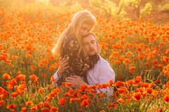 Man and woman embracing in poppy field on the dusk. Man and women embracing in poppy field on the dusk, countryside Malta royalty free stock photography