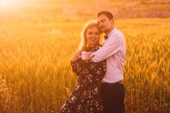 Man and woman embracing in poppy field on the dusk. Man and women embracing in poppy field on the dusk, countryside Malta royalty free stock image